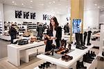 Woman choosing shoes in shop