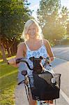 Woman on bike with dog in bike basket