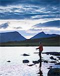 Man fishing in lake Sjuendevatnet at dawn