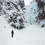 Man beside frozen waterfall in Fulufjallet National Park, Sweden