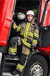 Firefighter standing in truck doors