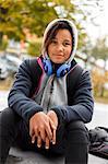 Portrait of girl with headphones and hood on