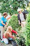 Grandparents and granddaughter working in garden