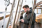 Man checking wallet on sailboat at Smogen