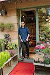 Florist standing in front of entrance of flower shop