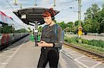 Woman wearing headphones on train platform