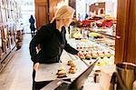 Baker putting baked goods in display window in Sweden