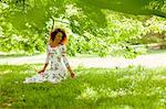 Woman in Floral Dress Kneeling under Tree in Garden