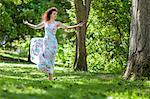 Woman in Floral Dress Dancing in Garden