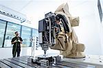 Apprentice robotics engineer with robot in robotics research facility