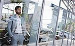 Serious, pensive car salesman looking out car dealership showroom window