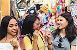 Happy young women with ice lollies in bazaar, Bangkok, Thailand