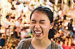 Tourist laughing in bazaar, Bangkok, Thailand