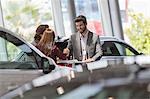 Car salesman handshaking with customers in car dealership showroom