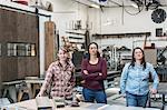 Three women standing in metal workshop, holding looking at camera.