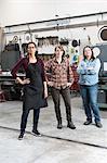 Three women standing in metal workshop, looking at camera.