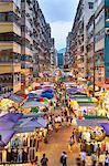 A busy market street in Mong Kok (Mongkok) lit up at dusk, Kowloon, Hong Kong, China, Asia