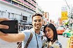 Young tourist couple taking smartphone selfie on street, Bangkok, Thailand