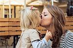 Mother kissing toddler daughter on park bench