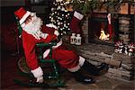 Santa Claus, sleeping in chair beside fireplace