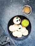 Traditional breakfast with Idli (rice cakes), coriander chutney, coconut chutney and coffee (South India)