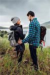 Couple standing beside Dillon Reservoir, using digital tablet, Silverthorne, Colorado, USA
