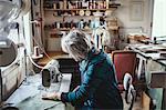 Senior female owner using sewing machine at workshop