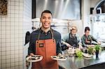 Portrait of smiling waiter holding fresh food plates against female chefs in restaurant kitchen