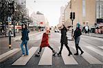 Full length of happy female friends crossing street in city