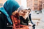 Female friends wearing hijabs sitting in city sharing digital tablet