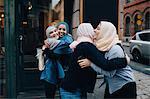 Smiling multi-ethnic female friends greeting on sidewalk in city