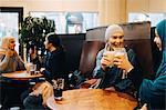 Happy female friends enjoying drinks at cafe