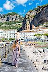 Amalfi, Amalfi coast, Salerno, Campania, Italy. Young woman strolling along the pier of Amalfi village