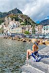 Amalfi, Amalfi coast, Salerno, Campania, Italy. Young woman sitting on the pier of Amalfi village