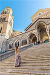 Amalfi, Amalfi coast, Salerno, Campania, Italy. A young woman climbs the staircase of the Amalfi cathedral