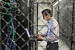 Hispanic man technician doing diagnostic tests on computer servers in a large server farm.