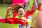 Enthusiastic boy runner crossing charity run finish line