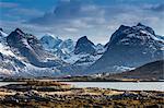 Snow on sunny, craggy mountains, Ramberg, Lofoten, Norway