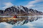Remote fishing hut at fjord waterfront below craggy mountains, Kleppstad, Austvagoya, Norway