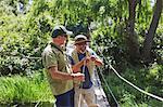 Active senior men friends fishing on footbridge