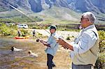 Active senior men friends fishing at sunny summer lake