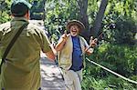 Playful active senior men friends fishing on footbridge