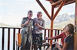 Happy active senior couples drinking wine on summer balcony