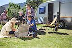 Active senior friends enjoying picnic outside camper van at sunny summer campsite