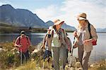 Active senior women friends hiking along sunny summer lake