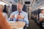Businessman drinking coffee on passenger train