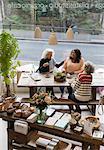 Women friends talking, drinking tea in shop
