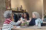 Women friends drinking tea in shop window