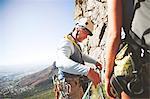 Male rock climber adjusting ropes