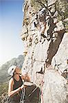 Female rock climber holding ropes for partner